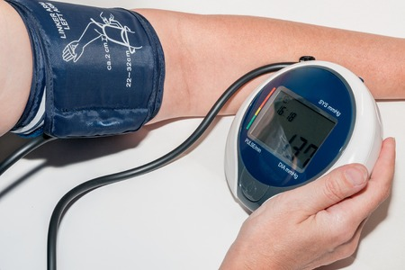 blood pressure unit: Sphygmomanometer measuring blood pressure on an arm Stock Photo