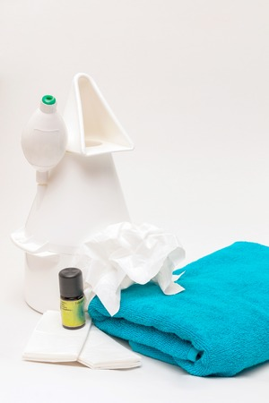 expedient: Vaporizer with eucalyptus oil, towel and paper-handkerchiefs in front of white background