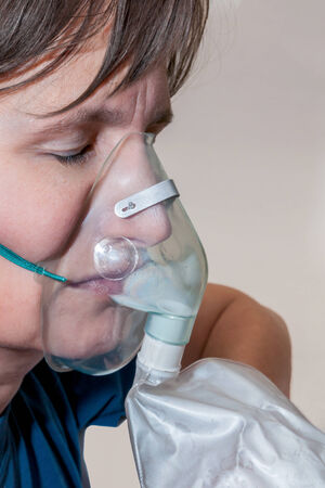 Head of a woman with hyperventilation mask and closed eyes photo