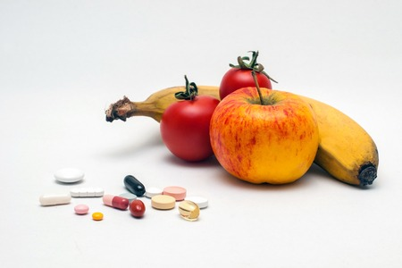 cut fruit: different colored tablets, apple, banana and tomatoes, isolated