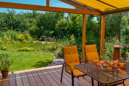 winter garden: View from a cozy winter garden in the large natural garden in summer Stock Photo