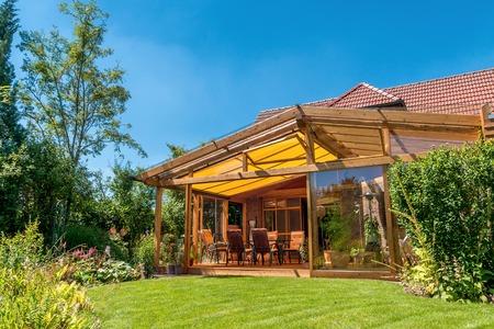 case moderne: Vista dal giardino estivo la natura in un accogliente giardino d'inverno