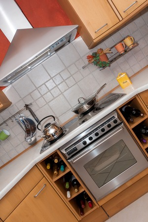 Diagonal view of a modern cooking area with stove, oven and chimney photo