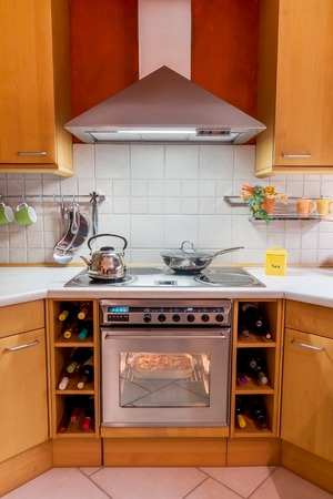 Diagonal view of a modern cooking area with stove, oven and chimney Imagens