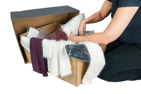unpacked: Cardboard with various packed and unpacked garments and partial view of a woman who inspects the goods, isolated