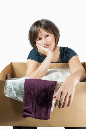 undetermined: exhausted woman has cardboardbox with clothes on her knees