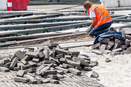work materials: Worker with protective vest paves the area between tram tracks Stock Photo