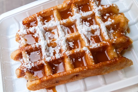 original plate: Belgian waffle with caramel syrup and powdered sugar Stock Photo