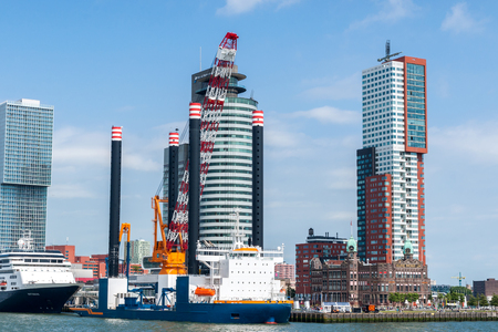 Rotterdam, Netherlands - June 21st, 2014: Rotterdam's modern architecture at Wilhelminapier overlooking a construction vessel for the construction of offshore wind farms and the MS Rotterdam VI