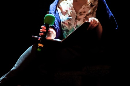 Professional lectrice with  microphone and book on a stage in spotlight