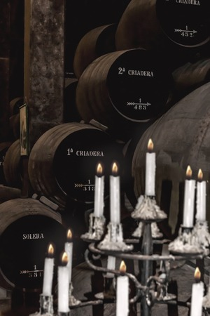 sherry: Stacked sherry barrels of a Solera with candlestick in the foreground