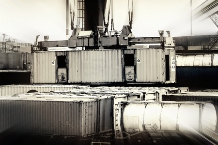 leveler: Closeup in a container terminal in the port of Rotterdam, Netherlands, while a container is loaded, desaturated colors