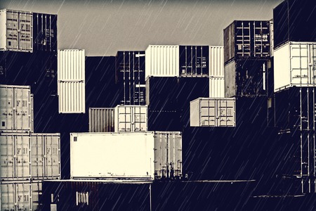 desaturated colors: Gloomy mood in the harbor - stack of containers in the rain with grain and desaturated colors