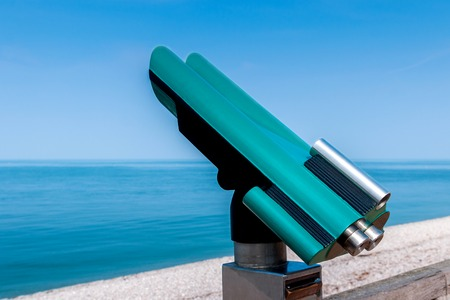 voyeur: Public telescope at seaside in turquoise colors and with copy space