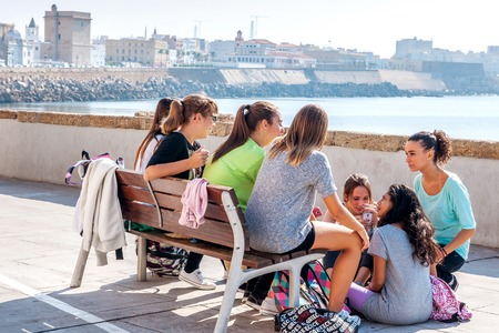 sidewalk talk: Cadiz, Spain - September 29th, 2014: A group of Spanish, female teenagers meet after school to talk together, in the background the skyline of Cadiz