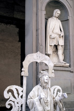 house robes: Florence, Italy - June 04th, 2006: Street artist in front of the Uffizi with a statue of the painter Giotto in a niche