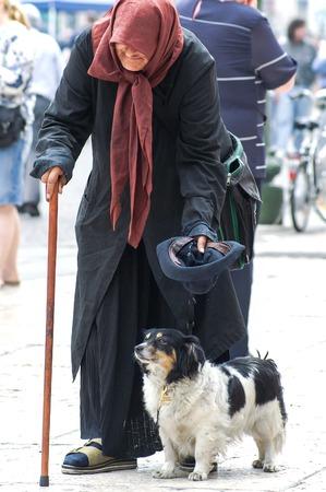 limosna: Verona, Italia - 27 de mayo de 2006: mendiga italiana vieja con el perro y el bastón presenta un sombrero vuelto hacia arriba hacia los transeúntes