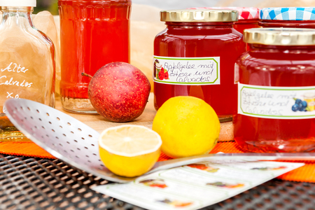 skimmer: Screw-top glasses with spiced apple jelly, label and skimmer standing on a table