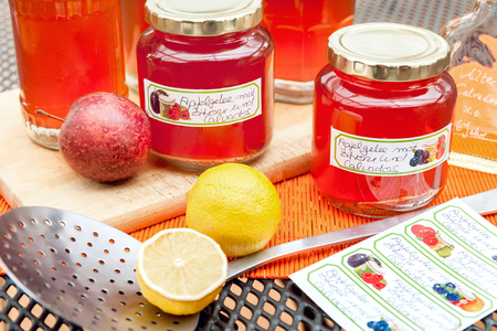 durability: Screw-top glasses with spiced apple jelly, label and skimmer standing on a table