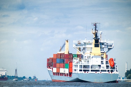 containership: A fully loaded containership enters the harbor of Hamburg, with copy-space