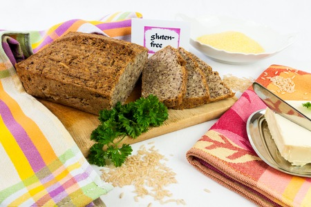 maize flour: Wooden board with homemade, gluten-free wholemeal bread from rice and corn, served with butter, isolated