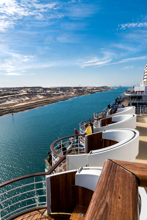 Sinai, Egypt - April 2nd, 2016: The Suez Canal - a ship convoy with a cruise ship passes the new eastern extension canal, opend in August 2015, coming from the direction of the great Bitterlake. President al-Sisi initiated the construction to boost the eg