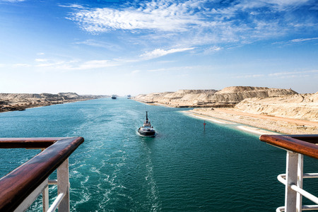The Suez Canal - a ship convoy with a cruise ship passes through the new eastern extension canal, opened in August 2015, landscape format with a ship´s rail in the foreground to the left and right side Stok Fotoğraf