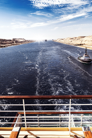 sinai desert: The Suez Canal - a ship convoy with a cruise ship passes through the new eastern extension canal, opened in August 2015, portrait format with a ship´s rail in the foreground Editorial