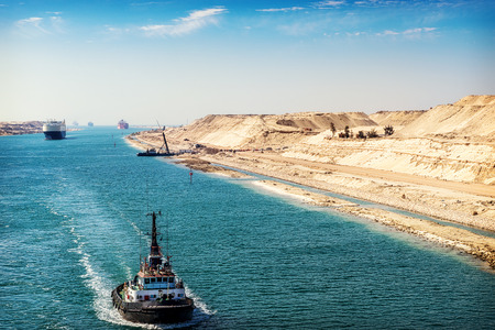 sinai desert: The Suez Canal - a ship convoy passes through the new eastern extension canal, opened August 2015,  a tugboat in the foreground Stock Photo