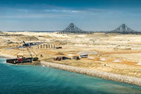 Uitzicht vanaf het onlangs geopende uitbreidingskanaal van het Suezkanaal naar de El Ferdan-brug en de resterende bouwwerkzaamheden aan het kanaal op de voorgrond