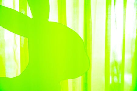 Happy Easter - part of a bright green plastic rabbit in front of green-white background