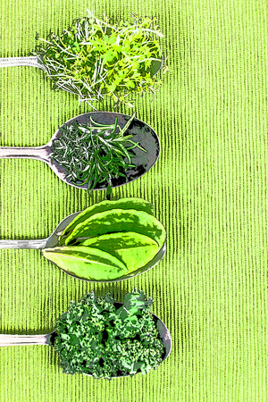 Vitamins - various herbs on spoons lie on light green cloth, with copy space and photo filter