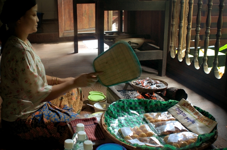 Santubong, Borneo, Malaysia - September 5th, 2010: Woman in the museum village Sarawak Cultural Village manufactures the traditional pastry Kuih Bahulu. People can learn everything about the indigenous tribes of Sarawak in the Cultural Village.