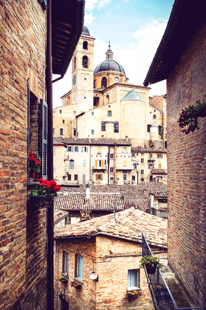 View through the medieval, narrow streets of Urbino to the Palazzo Ducale, Marches, Italy, Portrait format