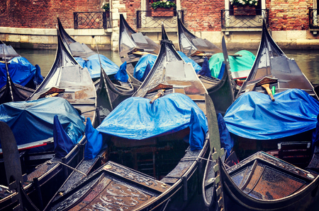 Several of Venices gondolas are moored in a canal while it is raining, Italy
