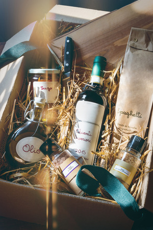 Italian specialty gift package with red wine, spaghetti, oil, tomato sugo and spice-salt on straw, light reflex