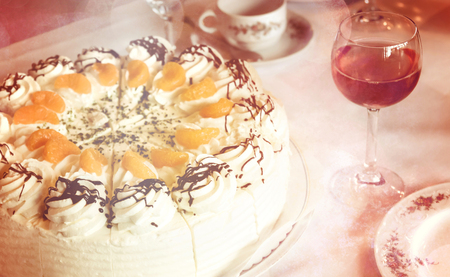 Part of a coffee table with tangerine-cream-cake, rosewine glass and tableware, vintage