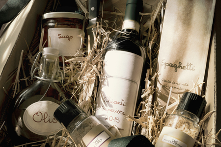 Italian specialty gift package with red wine, spaghetti, oil, tomato sugo and spice-salt on straw, vintage