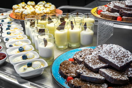 Selection of desserts at a dessert and cake buffet, served on stainless steel tables