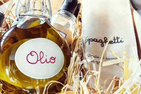 Italian specialty gift package with olive-oil and spaghetti on straw