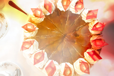 Top view on a plum-cream-cake with decoration of bright chocolate rhombuses, colored light reflections Imagens