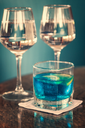 Long drink with blue curacao and two glasses of rosewine on shiny wooden table against turquoise wall