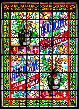 Fecamp  Normandy, France - September 23rd, 2014: Stained glass window in the Palais B?n?dine in portrait format with colorful depiction of the famous B?n?dine liqueur and its origins in the abbey of F?camp.