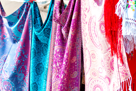 Closeup of colorful Portuguese fabrics and shawls in turquoise, pink and purple colors hung on a leash
