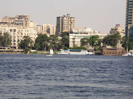 River Nile bank with a background of modern buildings on a sunny summer day and sailing boats, Cairo, Egypt