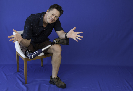 Middle-aged man with physical disability, happy with life sitting on the chair Archivio Fotografico