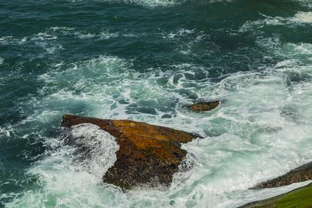 Sea waves breaking on a rocks in Brazil. Deep blue sea waves hit cliff. Sea waves hit rocks cliff. Mighty sea waves breaking on a cliff. Waves splashing over rocks. Strong ocean waves hitting rocks