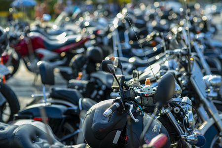 Front wheels of motorcycles exposed in a parking lot. Several parked motorcycles. Stock Photo