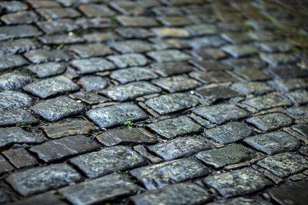 Stone pavement texture. Granite cobblestoned pavement background. Cobbled stone road regular shapes, abstract background of old cobblestone pavement close-up. Parallelepiped. Archivio Fotografico