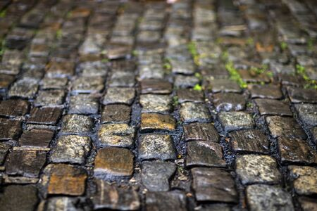 Stone pavement texture. Granite cobblestoned pavement background. Cobbled stone road regular shapes, abstract background of old cobblestone pavement close-up. Parallelepiped.